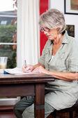 Senior woman writing notes at home — Stock Photo