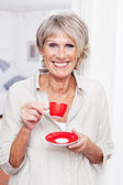 Vivacious older woman drinking espresso coffee — Stock Photo