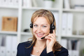 Female Customer Service Operator Using Headset In Office — Stock Photo