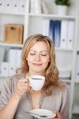 Affärskvinna håller kaffekoppen i office — Stockfoto