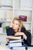 Bored Businesswoman Leaning On Stacked Binders At Desk — Stock Photo