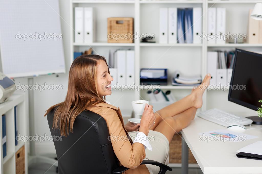 Businesswoman Having Coffee At Office Desk Stock Photo