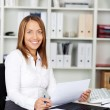 Young Businesswoman Holding Document At Desk — Stock Photo #25901925