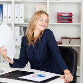 Businesswoman Fanning Herself With Documents At Desk — Stock Photo