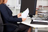Businesswoman Holding Graph Paper At Desk — Stock Photo