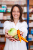 Pharmacist Holding Artificial Carrots Strawberry And Apple — Stock Photo