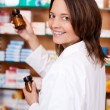 Female Pharmacist Holding Medicine Bottles While Looking over shoulder against shelves in pharmacy — Stock Photo