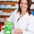 Female Pharmacist Putting Medicine Package In Bag At Counter — Stock Photo