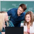 Confident Young Students With Laptop At Desk — Stock Photo