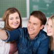 Friends Taking Self Portrait Through Mobile Phone In Classroom — Stock Photo #25913417