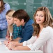 Teenage Girl Smiling With Teacher Assisting Classmates At Desk — Stock Photo