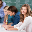 Stock Photo: Teenage Girl Smiling With Teacher Assisting Classmates At Desk