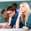Female Student Looking Up While Sitting With Classmates At Desk — Stock Photo #25917653
