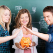 Girl Holding Piggybank While Friends Protecting It Against Chalk — Stock Photo #25917655