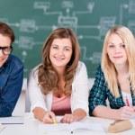 säker manliga och kvinnliga studenter leende medan du sitter på tabl — Stockfoto