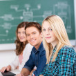 Confident Female Student With Classmates At Desk — Stock Photo