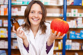 Female Pharmacist Holding Pill Bottle And An Artificial Apple — Stock Photo