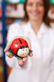 Pharmacist Holding Ladybird Shaped Coinbank — Stock Photo