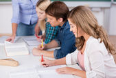 Writing Female Student With Classmates At Desk — Stock Photo