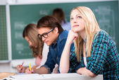 Female Student Looking Up While Sitting With Classmates At Desk — Stock Photo