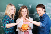 Girl Holding Piggybank While Friends Protecting It Against Chalk — Stock Photo