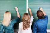 3 Teenage Students Writing On Chalkboard — Stock Photo