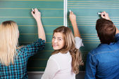 Teenage Student Writing On Chalkboard With Friends — Stock Photo