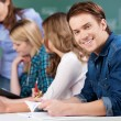 Male Student Holding Book With Classmates And Teacher At Desk — Stock Photo #25920087