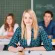 Female Student Sitting With Classmates In Classroom — Stock Photo