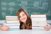 Female Student With Stack Of Books At Table — Stock Photo