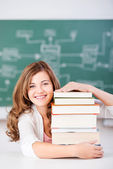 Female Student With Stack Of Books At Table In Classroom — Stock Photo