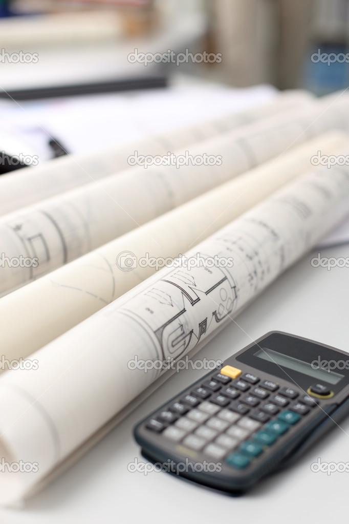 Calculator and rolled blueprints on desk stock photo for Blueprint estimator