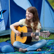 Girl Playing Guitar Against Tent — Stock Photo #25975187