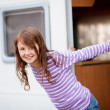 Stock Photo: Smiling Girl Standing At Caravan Entrance