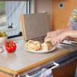 WomCutting Beadloaf At Cabinet In Caravan — Stock Photo #25976015