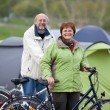 Stock Photo: Couple With Bicycles Standing Against Tent In Forest