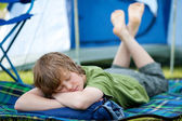 Boy Sleeping On Sleeping Bag With Tent In Background — Stock Photo