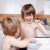 Boy Brushing Teeth While Looking At Brother In Bathroom — Stock Photo