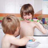 Menino escovando os dentes enquanto olha para o irmão na casa de banho — Foto Stock
