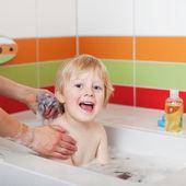 Chlapec sedí ve vaně zatímco matka mu ke koupání — Stockfoto