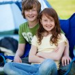 Siblings Sitting Together On Chair With Tent In Background — Stock Photo