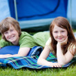 Brother And Sister Lying On Blanket With Tent In Background — Stock Photo