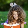 Girl Reading Book While Lying On Grass — Stock Photo #25989919