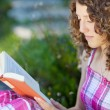 Teenage girl with curly hair reading a book — Stock Photo #25991947