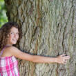 Girl with curly hair embracing a tree — Stock Photo