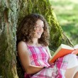 Teenage girl reading a book under a tree — Stock Photo