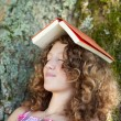 Stock Photo: Girl With Book On Head Napping On Tree Trunk