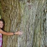 Happy Teenage Girl Embracing Tree — Stock Photo #25995727
