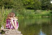 Teenage Girl Sitting On Rock While Looking Away By Lake — Stock Photo