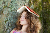 Girl With Book On Head Napping On Tree Trunk — Stock Photo